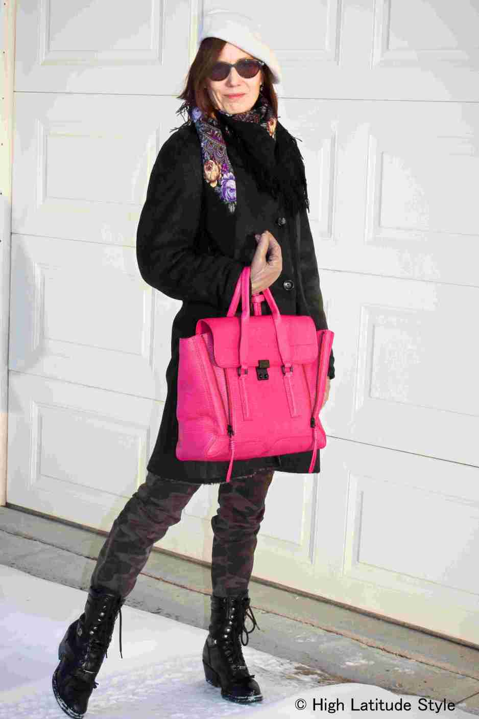 older woman wearing a neon pink bag