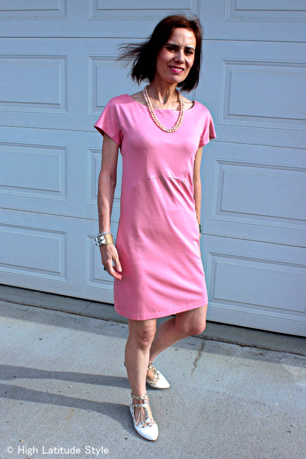 midlife woman looking posh chic in baby-pink jersey dress