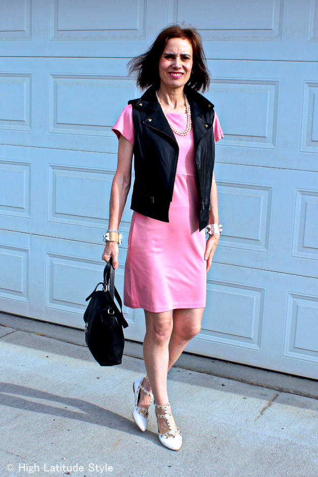 midlife woman in pink dress with leather vest