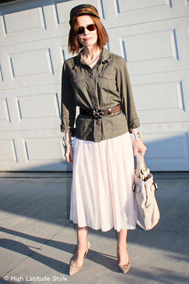 mature Streetstyle woman in layered mesh skirt and utility jacket