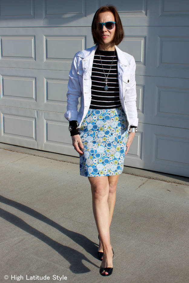 #over40fashion mature woman in floral print skirt with stripped top and white denim jacke