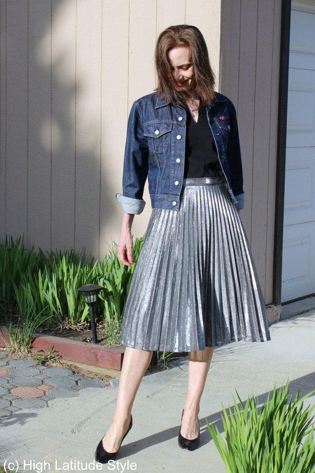 styleover50 mature woman in silver pleated skirt with denim jacket and pumps
