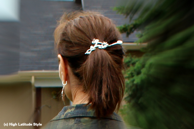 over 40 year old with high ponytail hold by a barrette