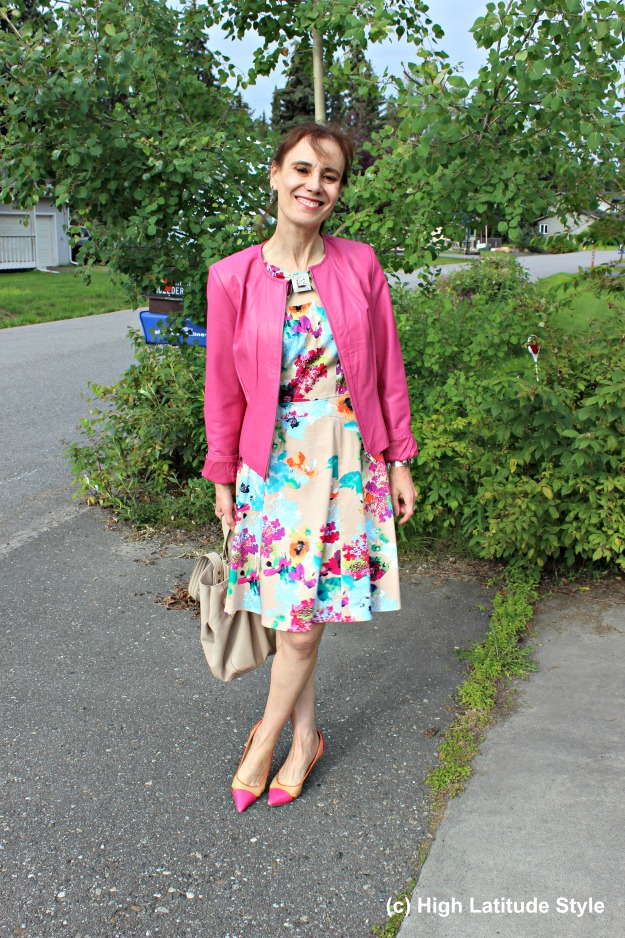 #fashionover40 mature woman in pink leather jacket and printed dress with pink and yellow