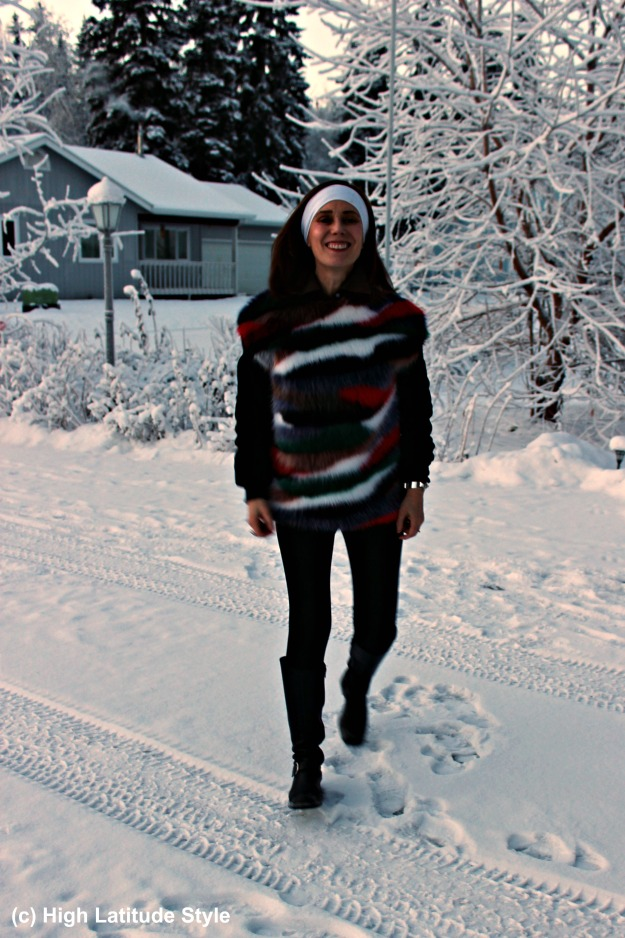 mature fashion woman in riding boots and sweater in the snow