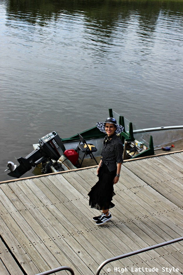mature style woman in black and white outfit on a dock