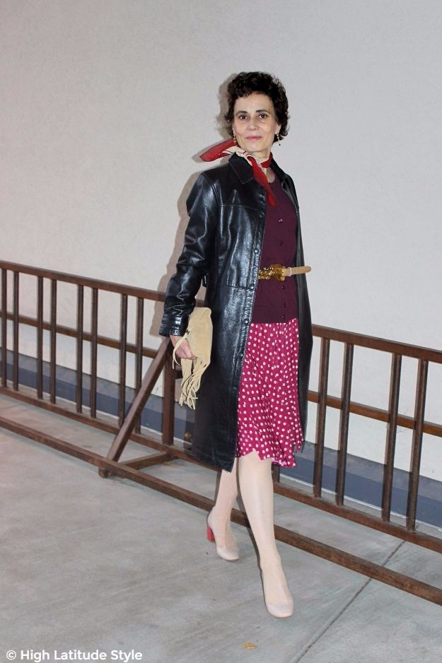 posh chic woman over 50 in skirt and cardigan with leather coat