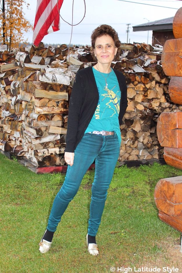 midlife woman in casual OOTD in front of firewood
