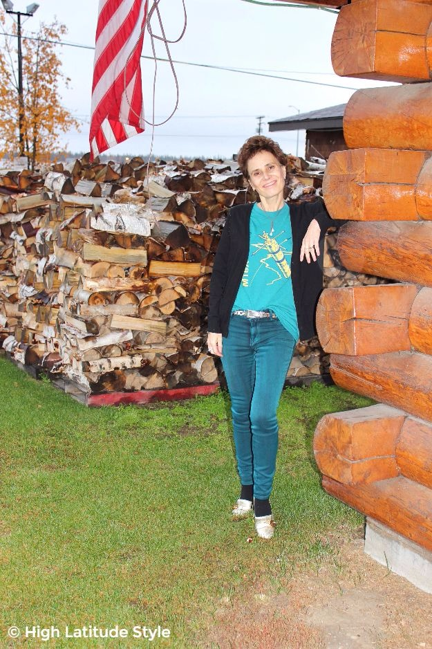 Alaskan woman in front of a wood log house