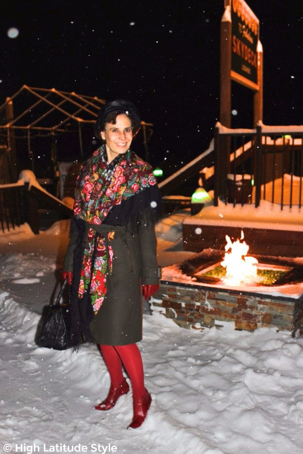 mature woman in winter outerwear in front of a fire