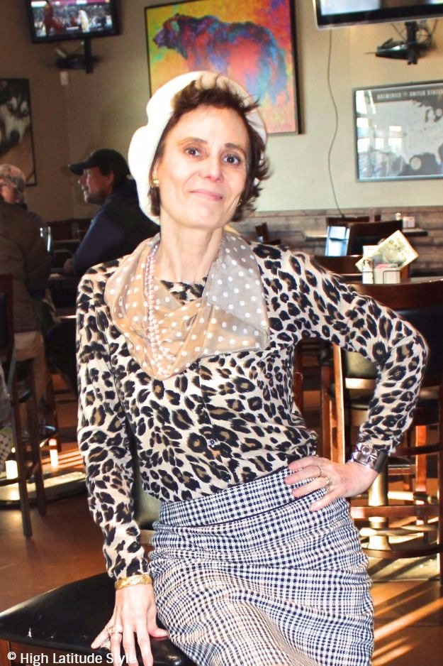 #advancedstyle #midlifestyle woman sitting in a bar with beret and mixed pattern look